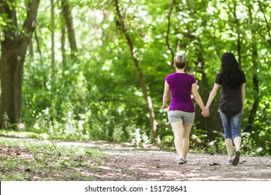 Girlfriends holding hands and walking in park, horizontal