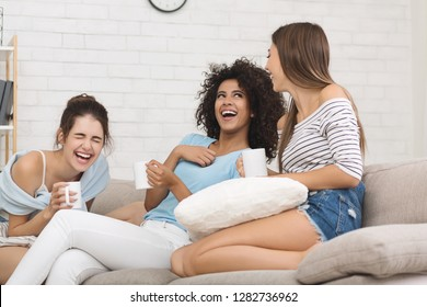Girlfriends laughing with jokes, drinking coffee, having home party