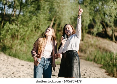 Girlfriends look to the sky and show a finger