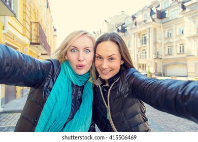 Girlfriends make a self portrait using her phone. Two women friends! Close-up portrait of young girls. Happy woman make picture together and having fun, laughing and make funny faces on camera. Travel