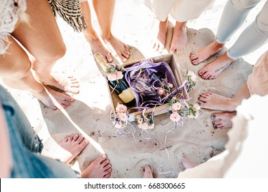 Girlfriends on sea beach on vacation. Sexy girls' legs on sand. Decorated box champagne, wine, glass. Decor of flowers. Close up. nature. Style boho. Party. Maiden evening Hen-parties. Bachelorette