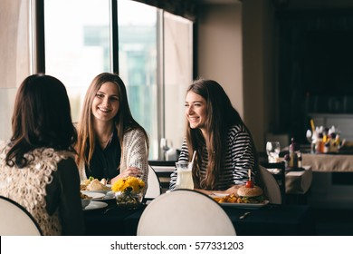 girlfriends out in town for drinks, lunch, spending quality time, eating tasty food and drinking together. Girls waiting  for friend to make important announcement getting excited to hear new secret.