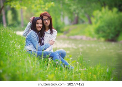 Girlfriends in the park, two young women near the lake, toned image with custom white balance, soft focus, and film grain effect