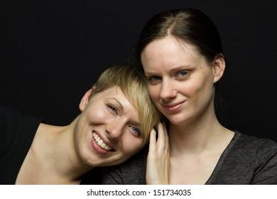 Girlfriends posing together in studio, horizontal