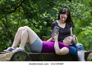 Girlfriends relaxing and using e-tablet at park, horizontal