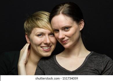 Girlfriends smiling in studio, horizontal