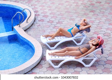 Girlfriends are sunbathing by the pool while relaxing in deck chair. Spend the weekend at the hotel getting sunny treatments. View from above