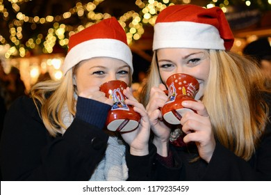 "Girlfriends visit Christmas market with many stalls and drink mulled wine from cups with the inscription ""Aachener Weihnachtsmarkt"" which means Aachen Christmas market"