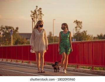 Girlfriends walk the dog and wear face masks