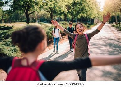 Girlfriends wearing backpack meet again in schoolyard on first day of school
