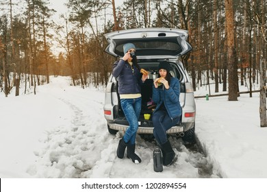 Girlfriends in winter wear on snowy day in the winter forest in the car having talk and drinking coffee