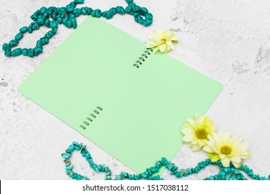 girlish flat lay with empty notebook or diary with green pages flowers and beads.