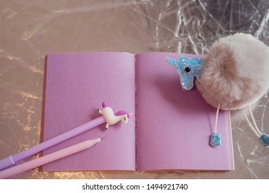 Girlish things still life. Notepad with purple pages, a fluffy ball keychain, unicorn pen, on silvery background. Close-up, shallow depth of field