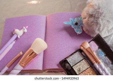 Girlish things still life. Purple pages notepad, fluffy ball toy, unicorn pen, sparkle eyeshadow palette, cosmetic brushes with twisted handles on silvery background. Close-up, shallow depth of field
