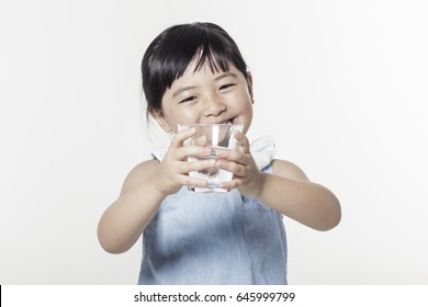 A girl(kid) hand hold a glass cup of clean water isolated white.