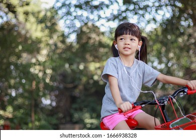 Girls aged 4 to 6 years, cute, long hair, pre-school age Riding a red bicycle With headphones listening to music Playing in the outdoor gardens, happy faces Beaming The background is green.