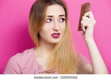 girls with anxious face combing hair with a wooden comb on a colored background, concept of beauty, body care, hair problems, hair  electrification