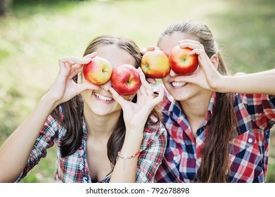 Girls with Apple in the Apple Orchard. Beautiful Girls with Organic Apple in the Orchard. Harvest Concept. Garden, Teens eating fruits at fall harvest.