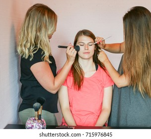 girls applying makeup to client