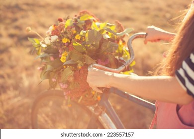 Girls arms holding an old bike handlebar with flowers basket