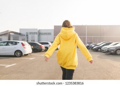 The girl's back in a yellow hoodie, walking along the street. Lookbook. Street fashion portrait
