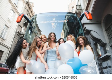 The girls with ballons stand near bus