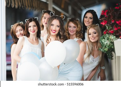The girls with ballons stand near flowers