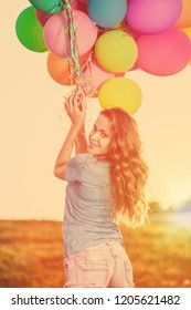 Girls with balloons at sunset. Stylish young women models against the sky celebrate a happy birthday.
