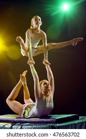 Girls in bathing suits athletes perform acrobatic element with support