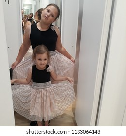 Girls in beautiful dresses in the fitting room of a clothing store.