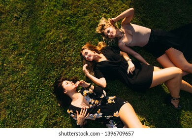 girls in beautiful dresses lie on the grass and smile. top view