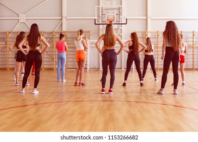 girls with beautiful figures in the gym are ready for fitness classes and listen to the instructions of their coach