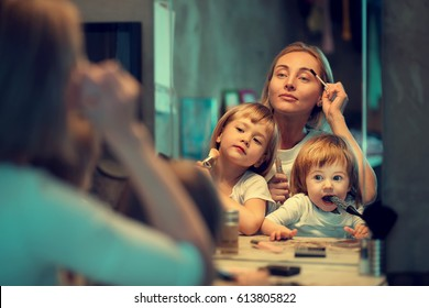 Girls are girls. Beautiful young mother is trying to do makeup with her two little daughters on her knees aping her. Image with selective focus and toning