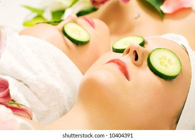 Girls in a beauty treatment with cucumber slices