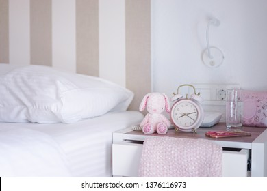 Girl's bedroom. A bed room of little girl with selective focus on the pink alarm clock next to the rabbit plush doll.