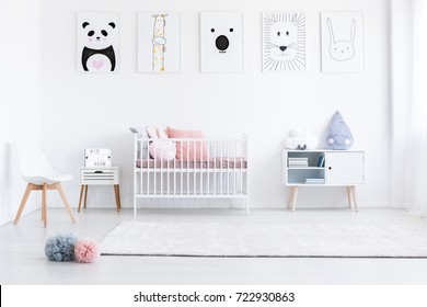 Girl's bedroom with pastel pompons on floor and pink pillows on bed against wall with drawings