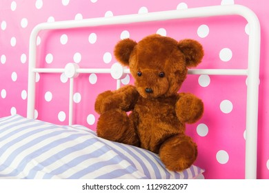 Girls bedroom with pink wall paper and stuffed bear