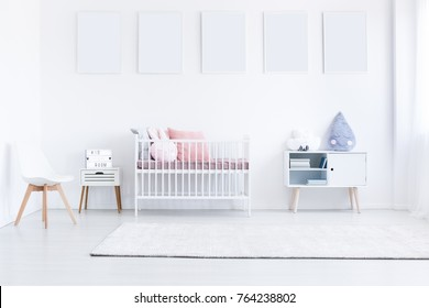 Girl's bedroom with white posters on wall above bed with pink bedsheets and cupboard with blue pillow