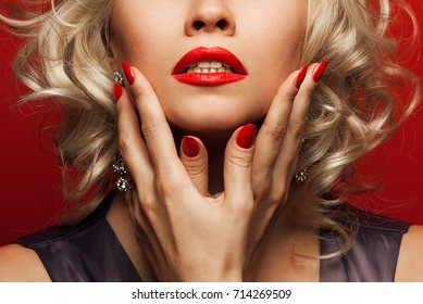 Girl's best friends and femme fatale concept. Marilyn Monroe style. Close up portrait of rich young woman smiling wearing expensive luxurious diamond earrings. Studio shot