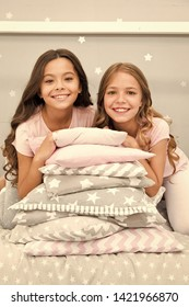 Girls best friends gather in bedroom for slumber party. Domestic party for kids. Girls near pile pillows posing with brilliant smiles. Lets start this party. Kids in pajamas prepare bedroom for party.