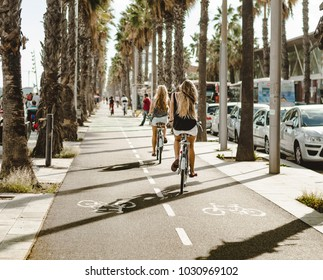 girls bike along the palm tree lane in Barcelona