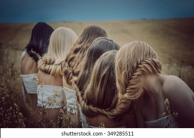 Girls blondes, redheads and brunettes closed hair in summer field