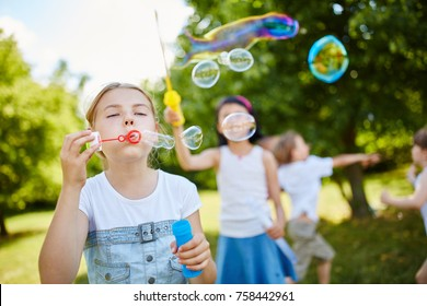 Girls blow fragile soap bubbles in the air in the park in summer