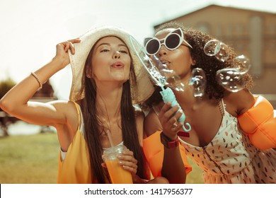 Girls blowing the bubbles. Close-up of radiant long-haired tanned beaming glowing cheerful young-adult ladies wearing trendy sunglasses engaging in blowing the bubbles