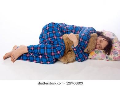 Girls in blue pajama sleeping on white