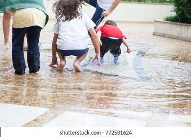 Girls and boy play on playground wet floor