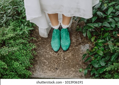 girl's bride's legs in green elf style shoes among bushes on the path