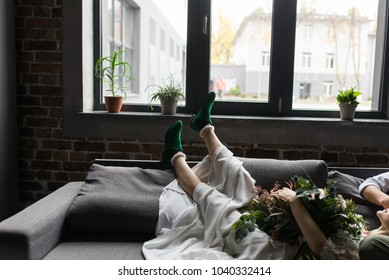 Girl's bride's legs in green elf style shoes on the sofa. The bride's legs in green stylish shoes
