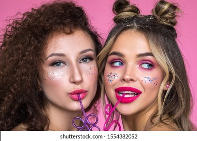 Girls with bright makeup on a pink background. Creative glitter makeup.