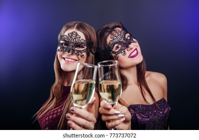 girls celebrating new years eve drinking champagne on masquerade party